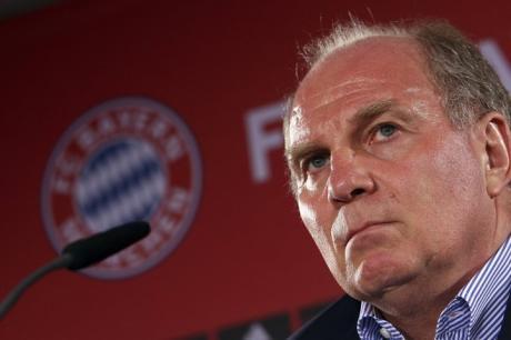 Uli Hoeness_in_front_of_Bayern_Munich_logo